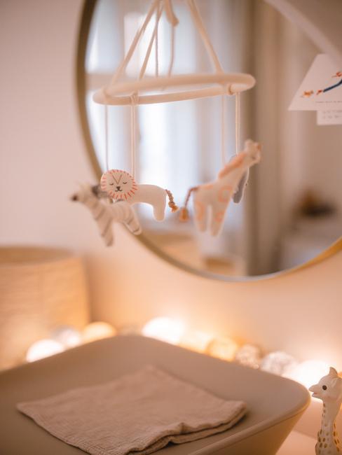 Zbliżenie na mobil ze zwierzątkami nad przewijakiem, przy okrągłym lustrze.