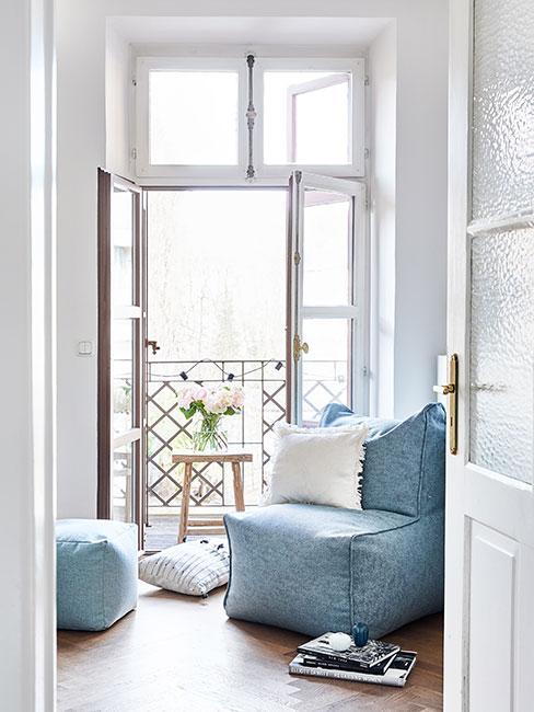 błękitny fotel typu worek z pufą przy wyjściu na mały balkon w bloku