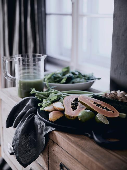 Zbliżenie na talerz z owocami oraz dzbanek z zielonym smoothie