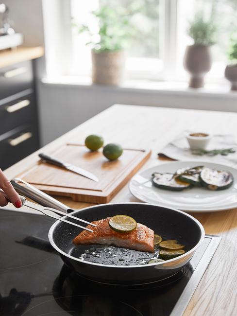 Zbliżenie na patelnię z łososiem, drewnianą deskę do krojenia z nożem oraz dwa białe talerze