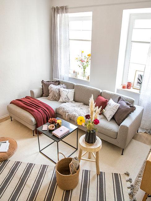 Mały salon z szarą sofą narożna w stylu skandynawskim i naturalnymi meblami i tekstyliami w ciepłych kolorach