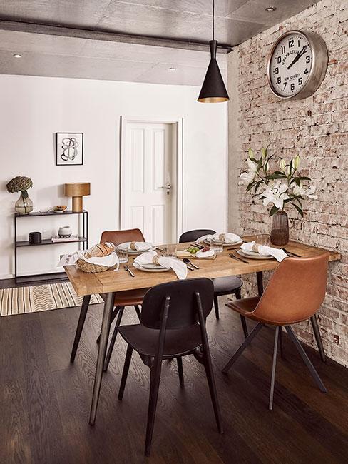 Jadalnia w stylu industrialnym z obnażoną ścianą, stołem zdrewna na czarnych nogach i krzesłami w różnych kolorach: brązowym i czarnym