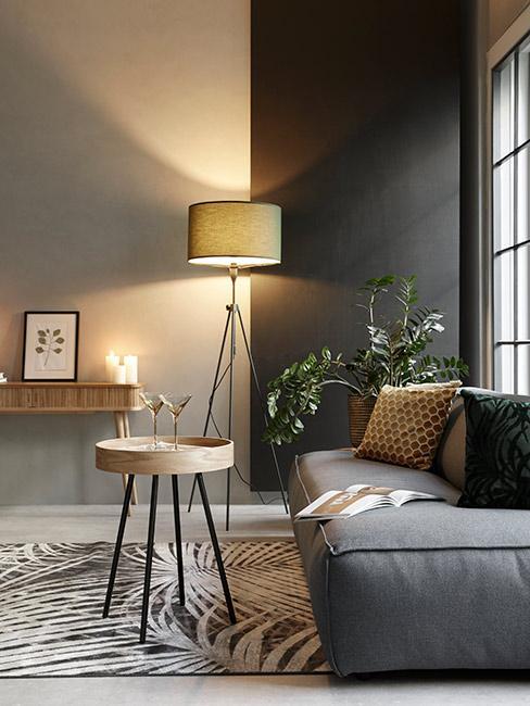 Ciemny salon w stylu industrialnym z szarą sofą modułową i drewnianymi meblami