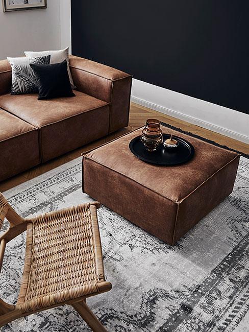 Zbliżenie na dużą pufę ze skóry i sofę modułową ze skóry na szarym dywanie vintage