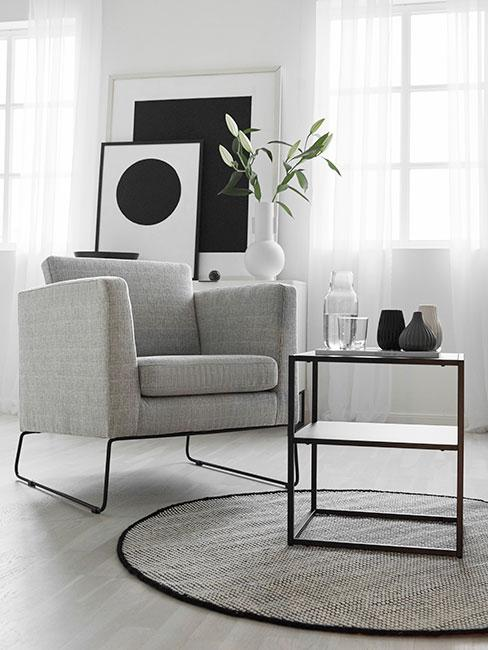 szary nowoczesny fotel w jasnym minimalistycznym salonie z nowoczesnymi obrazami na konsoli