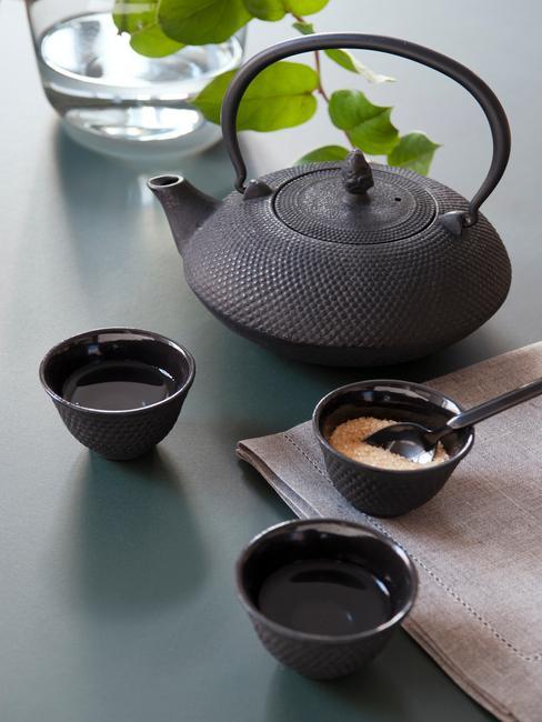 Czarny imbryk na harbatę w stylu orientalnym z dwoma czarnmi kubeczkami na stole