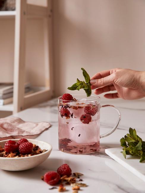 Zbliżenie na szklankę z owocową herbatą na blacie kuchennym obok miseczki