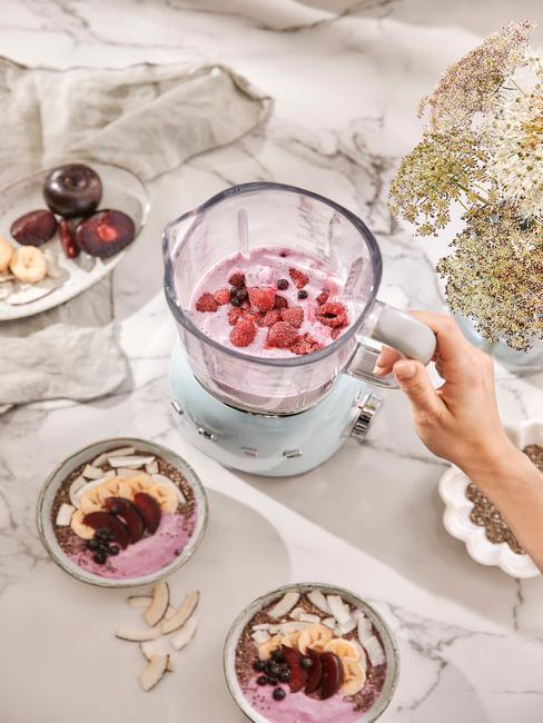 Mikser ze smoothie na blacie kuchennym oraz miseczki i białego talerza z owocami