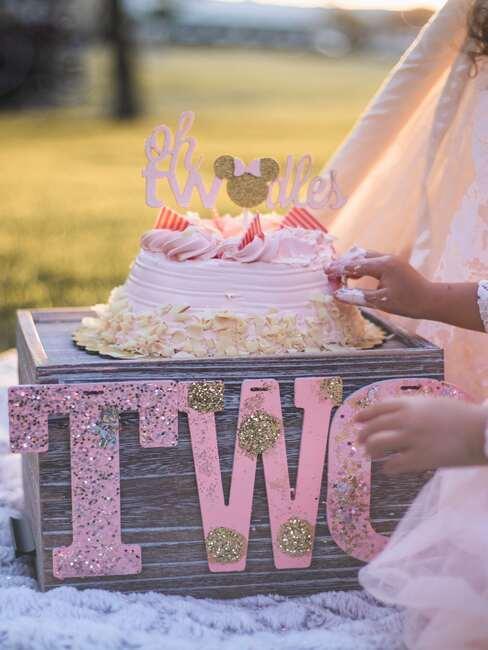 Zbliżenie na tort urodzinowy dla dziewczynki na przyjęcu zorganizowanym na świeżym powietrzu