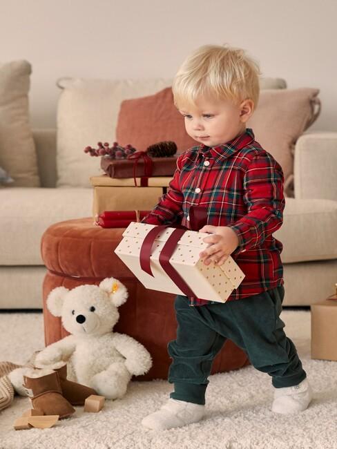 Chłopczyk stojący na białym dywanie obok pomarańczowego pufu