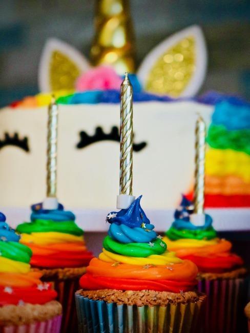 Zbliżenie na muffinki udekorowane kolorowym kremem ze świaczkiami oraz tort w kształće jednorożca