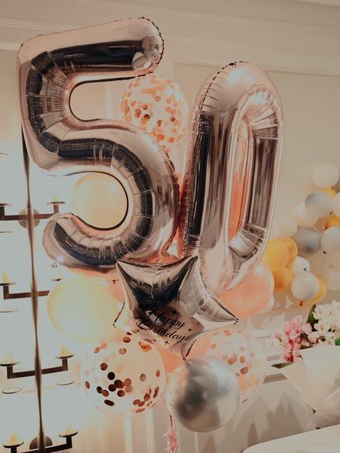Dekoracje na 50. urodziny z dużą ilością balonów w salonie