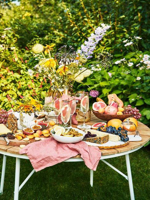Okrągły, drewniany stół z bukietami kwiatów, zastawą oraz przekąskami