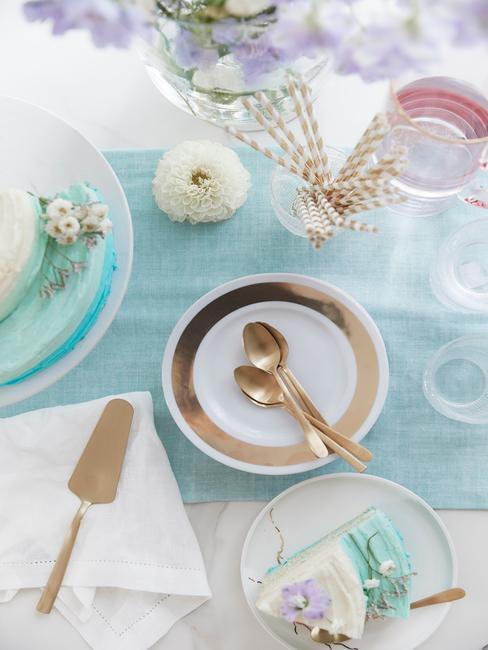 Zbliżenie na udekorowany stół urodzinowy z turkusowym bieżnikiem, szklanym wazonem z kwiatami, tortem oraz biało - złotą zastawa