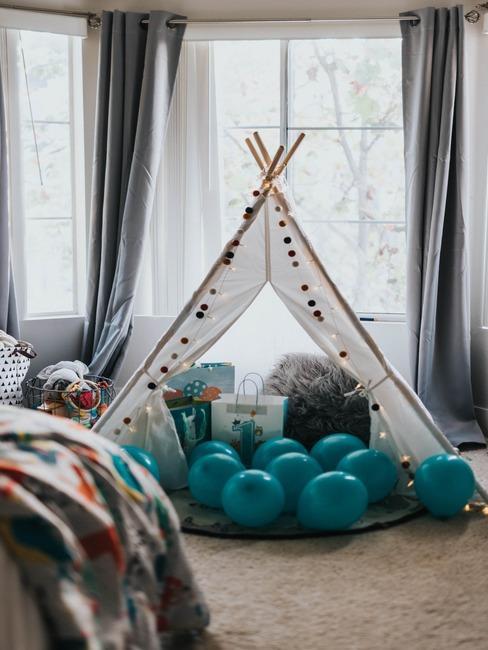 Namiot tipi w pomieszczeniu z prezentami oraz niebieskimi balonami