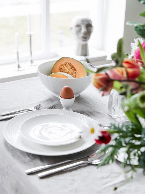 Zbliżenie na biały zestaw śniadaniowy na stole z brunchem oraz wazonem kwiatów