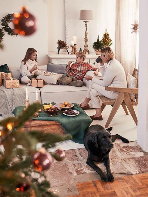 Rodzina w świątecznym salonie na dużej beżowej sofie modułowej z czarnym psem i choinką n apierwszym planie