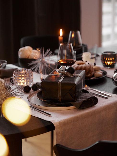 zbliżenie na prezent na świątezcnym stole w czarnym opakowaniu i złotą wstążką