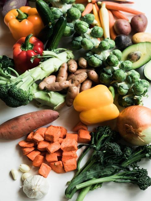 Wiele warzyw ułożonych na białym blacie