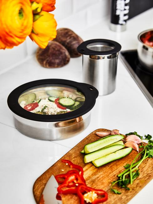 Drewniana deska z warzywami oraz dwa pojemniki na żywność