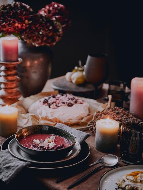 Zastawiony stół z zastawa talerzy z zupą, deserem oraz świeczkami
