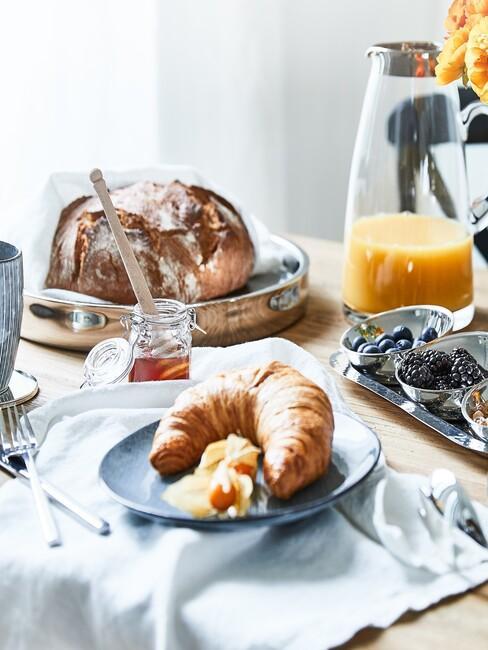 Drewniany stół z zastawą niebieskich naczyń w stylu scandi z pieczywem, dzbanek z sokiem oraz obrus