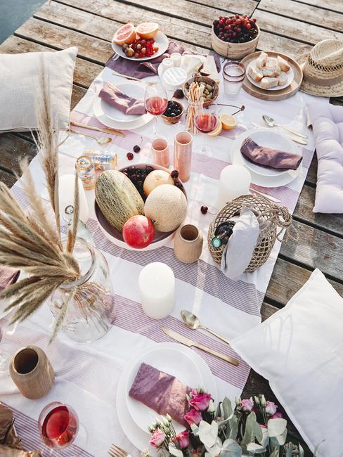 Letni brunch na pomoście z dekoracją w wazonie, misą z owocami oraz talerzykami