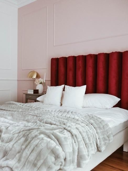Elegancka sypialnia z różową ścianą i łóżkiem z bordowym zagłówkiem
