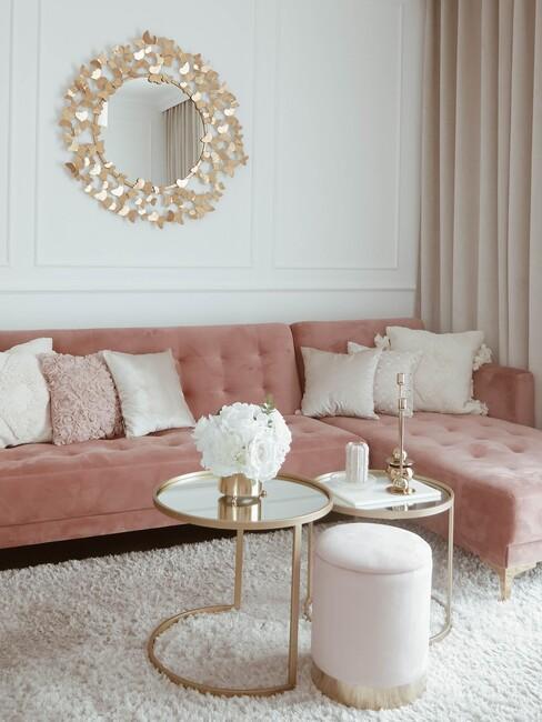 Salon z różową sofą, lustrem w złotej ramie i stoliki kawowe