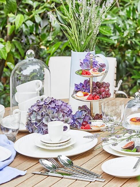 Zbliżenie na okrągły, drewniany stół na zewnętrz z białą zastawą talerzy, szklaną patera oraz ciastkami