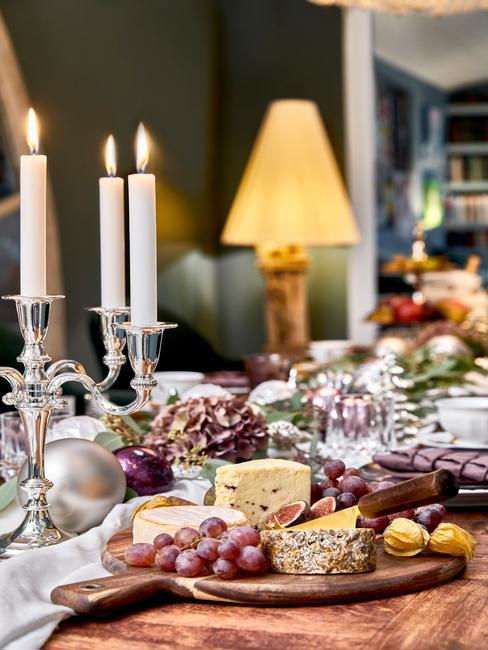 Stół udekorowany na przyjęcie świąteczne ze srebrnym świecznikiem, owocami, deską serów, lampą oraz kwiatami