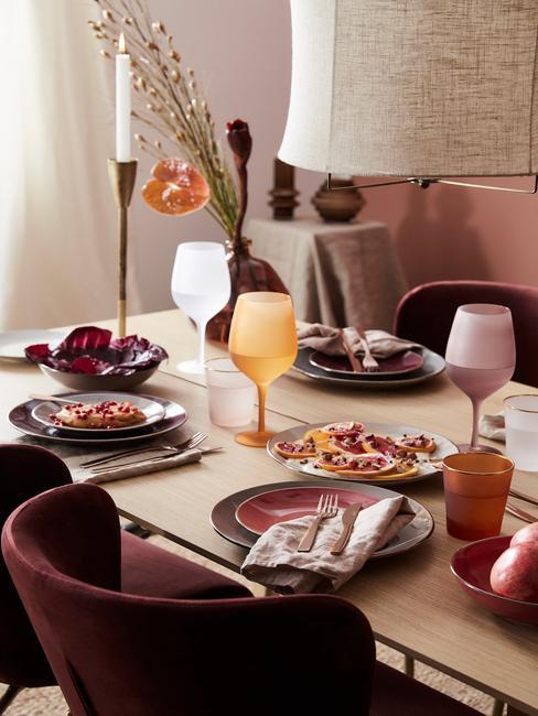 Drewniany stół z szarymi talerzami, kolorowymi kieliszakmi oraz świeczniami