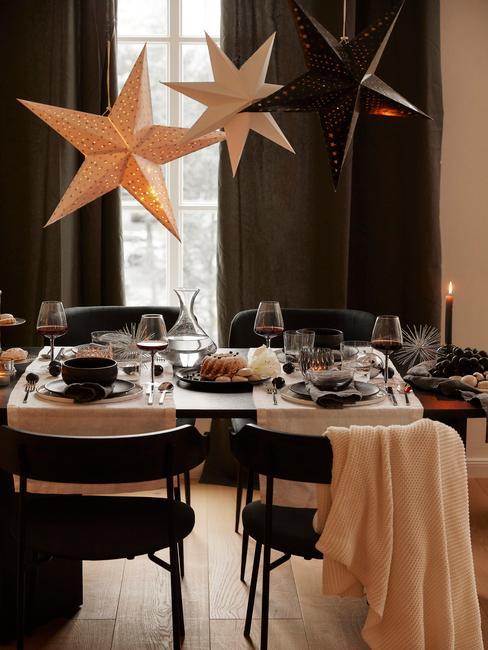 Czarny stół z dwoma, białymi bieżnikami, zastawą stołową, kieliszkami, świeczkami, oraz gwiazdami nad stołem jako dekoracja