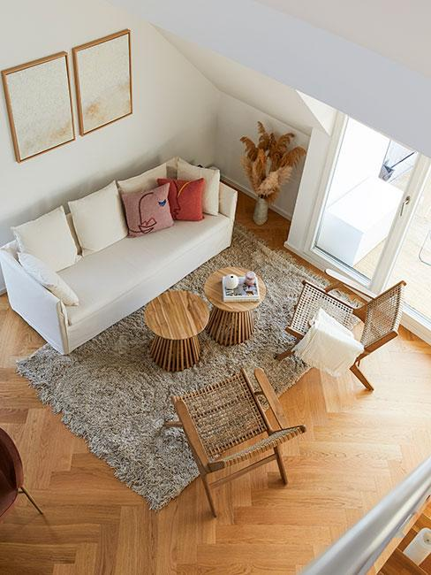 Niwielki salon w donmu z wysokim stropem z viałą sofą i jasnymi meblami z drewna