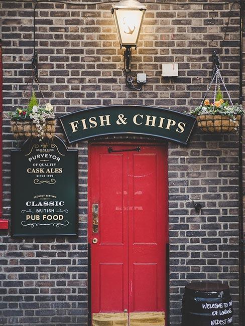 Wejscie do pubu z szyldem Fish and Chips