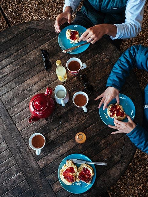 Widok z góry na osoby jedzące brytyjskie wypieki scones z śmietaną i dżemem