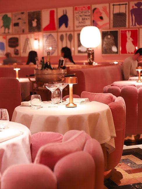 Kawiarnia z różowymi tapicerowanymi fotelikami z akasmaitu w kształcie muszelek i okrągłymi stoliczkami