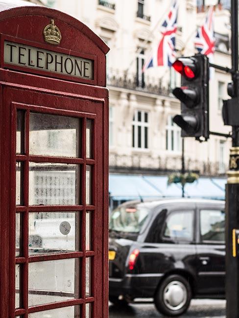 zbliżenie na czerwoną budkę telefoniczną na tle czarnej londyńskiej taksówki