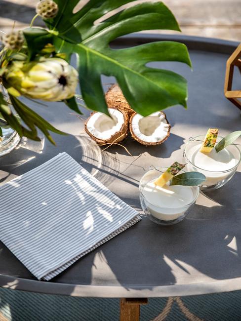 Szary stół zewnętrzny z drinkami z kokosu, liściem monstery w wazonie oraz lniana ścieraczka