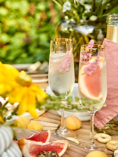 Zbliżenie na dwa kieliszki do szampana z drinkiem na drewnianym stole obok wazonu z kwiatami