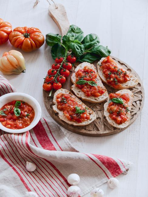 Drewniana deska do krojenia z bruschettą obok miseczki z sosem poidorowym