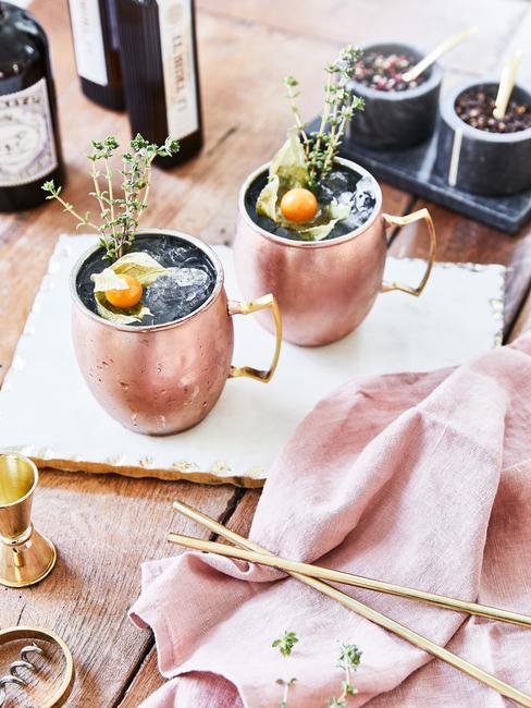Dwie miedziane szklanki do moscow mule na desce obok różowej ściereczki
