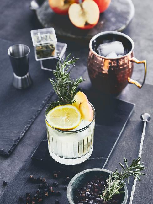 Zbliżenie na szklankę z ginem i tonickiem na czarnej desce na blacie