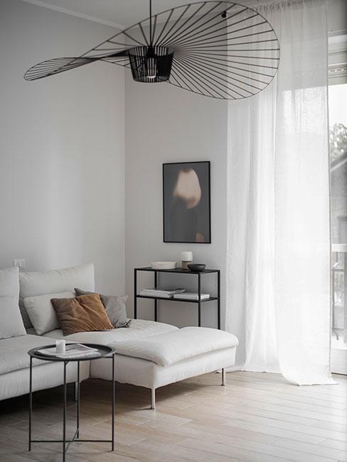 Minialistyczny salon z popielatą sofą z aksamitu i ażurową czarną lampą wiszącą z metalu
