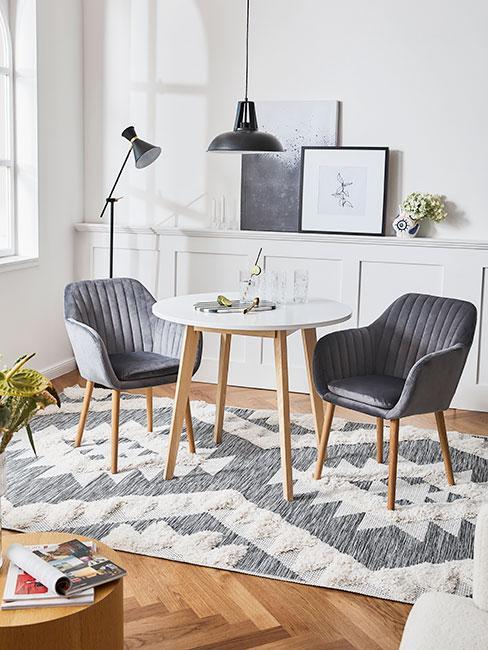 Mała jadalnia z białym okrągłym stołem, dwoma szarymi krzesłami na tle białej komody