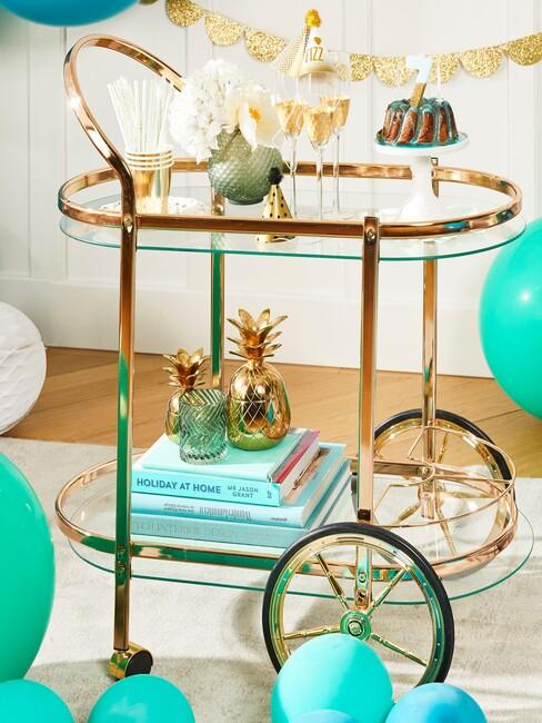 Szklany wózek barowy ze złotym wykończeniem, dekoracją z książek iraz kieliszkami i ciastem