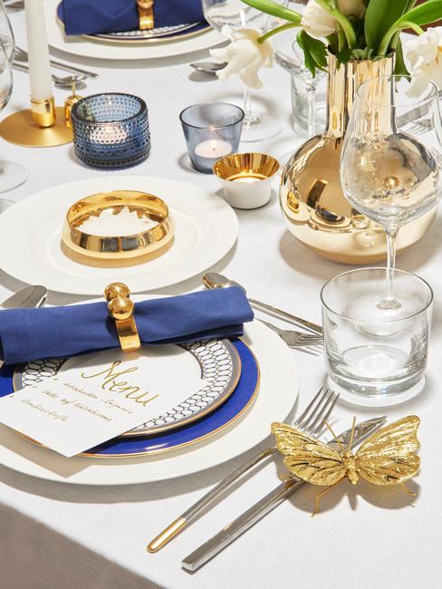 Stół z białym obrusem, złotymi dekoracjami i niebieskimi akcentami w postaci serwetek oraz świeczników