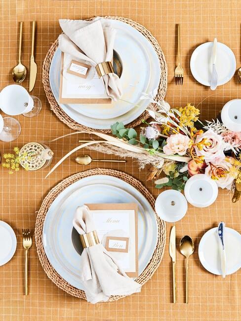Widok na zastawiony stół z wazonem kwiatów, złotymi sztućcami oraz białymi talerzami