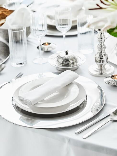 Stół w białej tonacji: obrus, talerze oraz srebrnymi dekoracjami w postaci świecznika