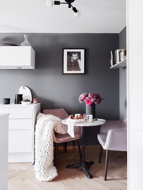 Biała kuchnia z mała jadalnią z okrągłym stołem i dowma różowymi krzesłami na tle szarej ściany